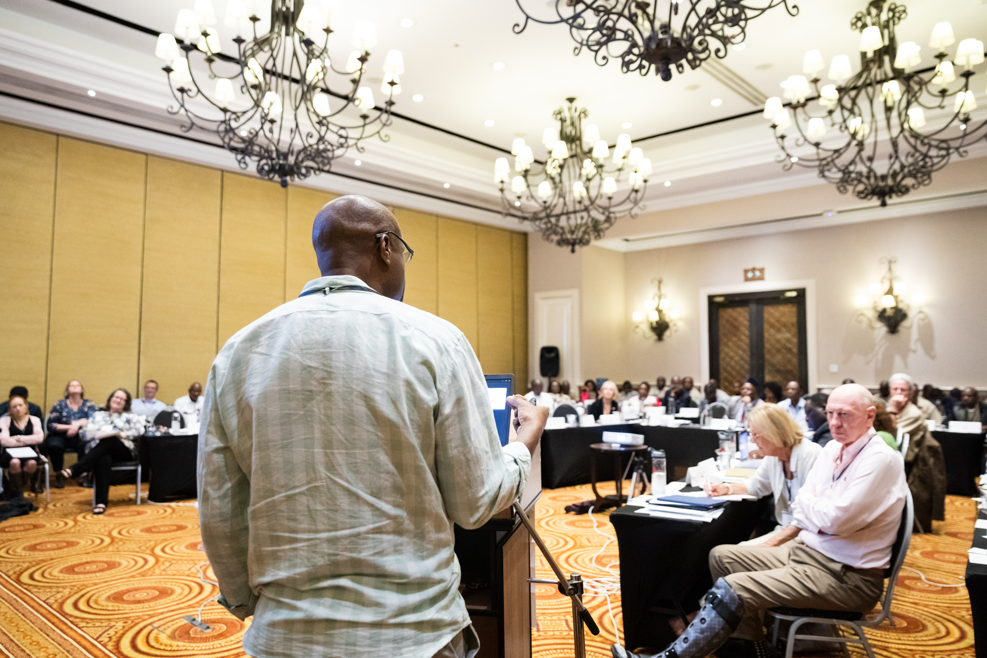 Dr. Kelly Chibale presents at the Isdell:Flowers Cross Border Malaria Initiative's 2020 Round Table in Livingstone, Zambia. Neville Isdell, donor to the H3D, is seen listening intently on the right.